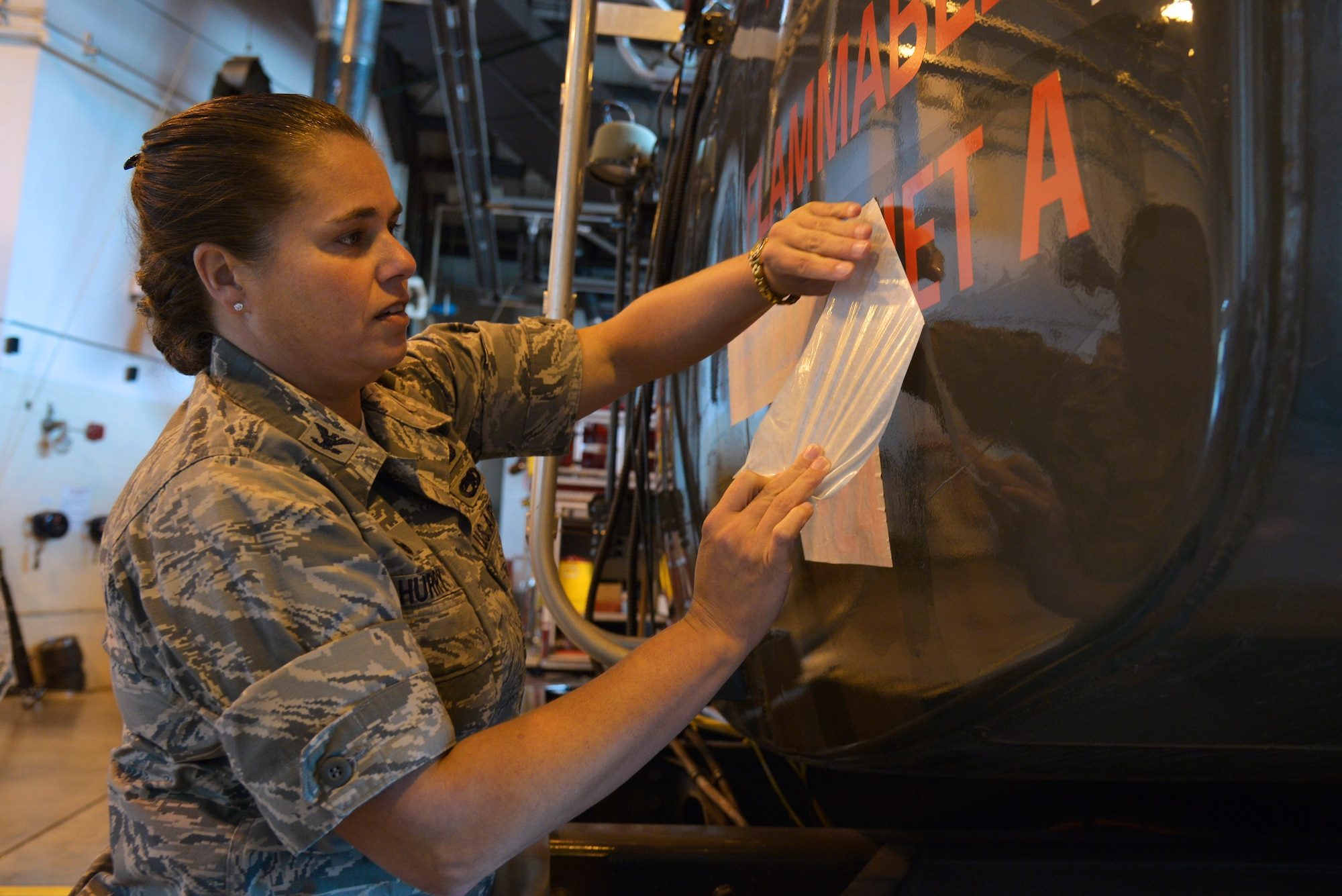 Col. Linda Hurry applies the Jet A1 fuel sticker on an R11 refueler as part of the conversion from JP8 fuel to Jet A1 fuel Oct. 15, 2014, Scott Air Force Base, Ill. Jet A1 fuel was created as a cost savings measure by the Department of Defense and will save approximately $40 million dollars annually. Hurry is the 635th Supply Chain Operations Wing commander. (U.S. Air Force photo/Tech Sgt. Christopher Boitz)
