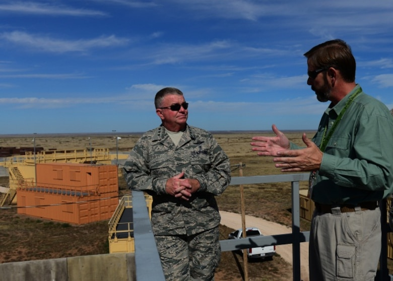 Steven Coffin, Melrose Air Force Range manager, briefs Lt. Gen. Thomas Travis, Surgeon General of the Air Force, on the assets that allow special operators from across the Department of Defense to practice Military Operations on Urban Terrain Oct. 28, 2014, at Melrose Air Force Range, N.M. This MOUT site provided a simulated urban combat environment to Cannon medics competing in the Commando Challenge during September's Emergency Medical Technicians rodeo. (U.S. Air Force Photo/Airman 1st Class Shelby Kay-Fantozzi)