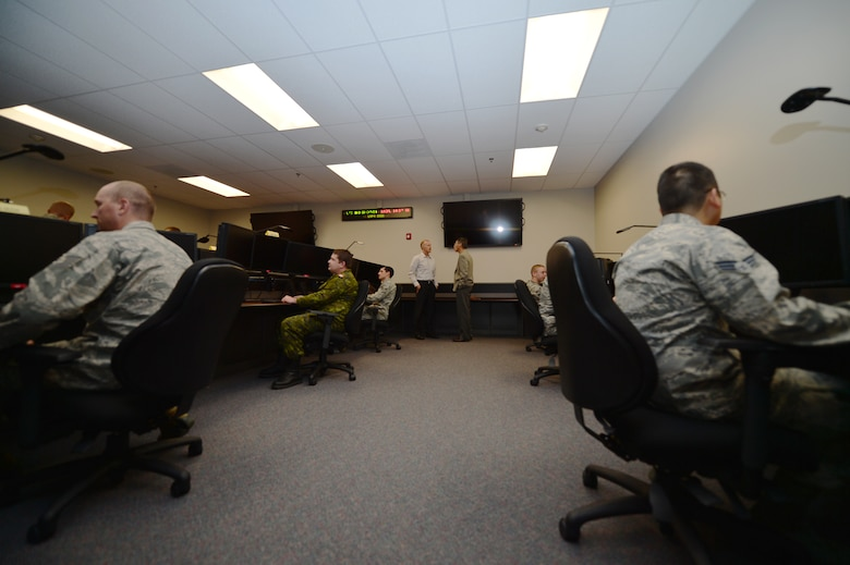 After completing a missile warning demonstration, members from the 460th Operations Group sit at their workstations in the new standardized space trainer Oct. 29, 2014, on Buckley Air Force Base, Colo. The new SST, which is one of two on base, houses 12 workstations and is designed to streamline the training process for 460th Space Wing space operators. (U.S. Air Force photo by Senior Airman Darren Scott/Released)