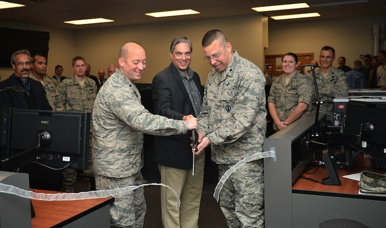 From left, Lt. Col. John Mizell, Space and Missile Systems Center material leader, Jeff Drake, Lockheed Martin Block 10 program manager, and Lt. Col. Timothy Bos, 460th Operations Support Squadron commander, cut a ribbon during the unveiling of a new standardized space trainer Oct. 29, 2014, on Buckley Air Force Base, Colo. The new SST houses 12 workstations and is designed to streamline the training process for 460th Space Wing space operators. (U.S. Air Force photo by Senior Airman Darren Scott/Released)