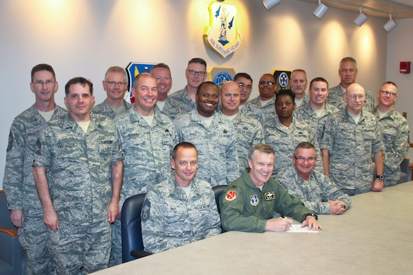 The 127th Wing Chiefs Council surround Col. Philip Sheridan, 127th Wing commander, as he signs the approval for Building 409 to be used as the Enlisted Heritage House at Selfridge Air National Guard Base on October 31, 2014.  The facility will be used for enlisted council meetings and host a heritage room, featuring photos and other information about the contributions of Michigan Air National Guard enlisted Airmen. (U.S. Air National Guard photo by Tech. Sgt. Dan Heaton)
