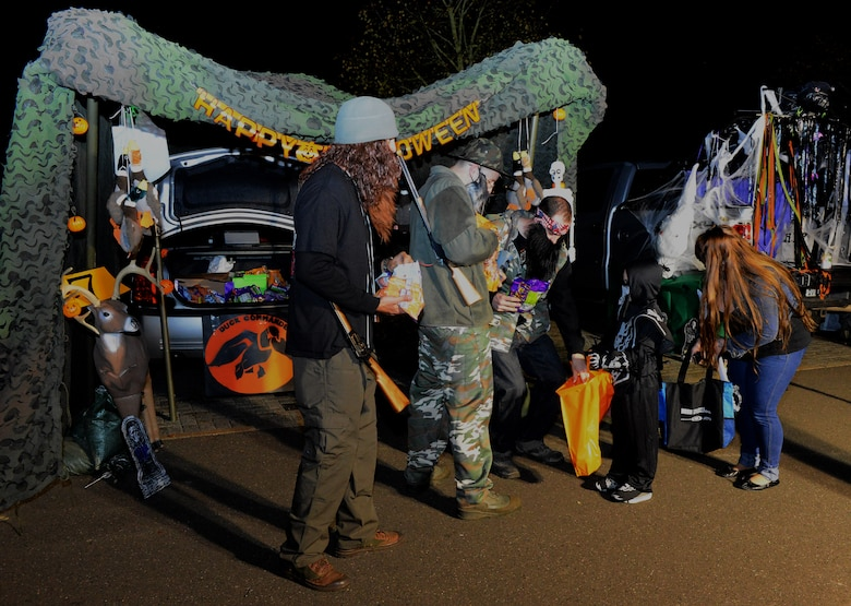 "Volunteers for Family Fright Night hand out candy to a trick-or-treater for ""Trunk-or-Treat"" at the Club Eifel parking lot on Spangdahlem Air Base, Germany, Oct. 30, 2014. ""Trunk-or-Treat"" allowed trick-or-treaters and their family members to safely get candy from the trunks of decorated vehicles. (U.S. Air Force photo by Airman 1st Class Luke Kitterman/Released)"