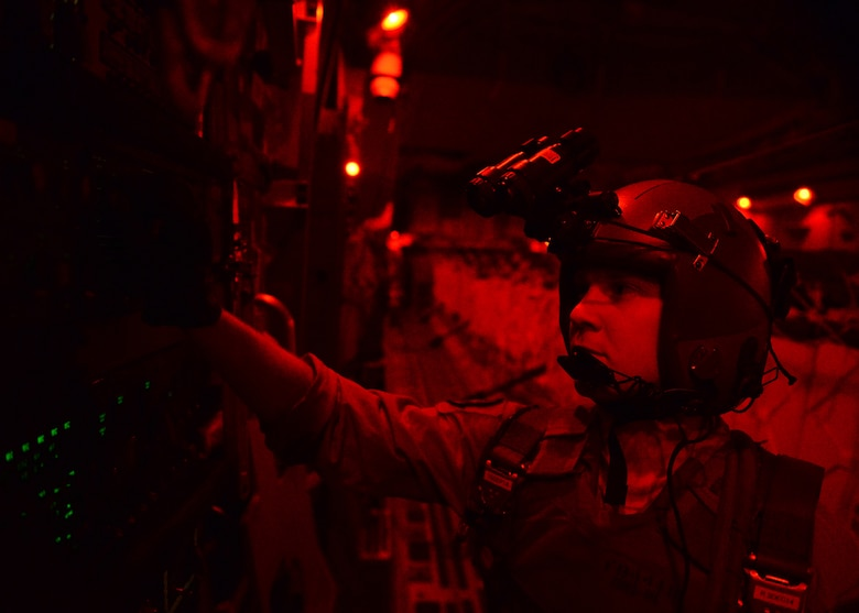 Senior Airman Paul Maginnis prepares to open the back door on a C-17 Globemaster III during a humanitarian air drop of 40 container delivery system bundles filled with fresh drinking water  Aug. 31, 2014, over the area of Amirli, Iraq. Lights are dimmed or shut off completely to lower visibility to threats from the ground. The airdrop included two C-17s and two C-130 Hercules delivering 10,545 gallons of fresh drinking water and 7,056 Halal Meals Ready to Eat. Maginnis is a 816th Expeditionary Airlift Squadron loadmaster. (U.S. Air Force photo/Staff Sgt. Shawn Nickel)