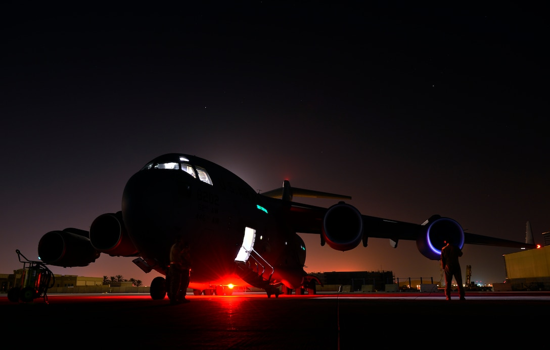 Senior Airman Jon Woerzburger awaits engine start prior to a Aug. 30, 2014, humanitarian airdrop mission over Amirli, Iraq. The two C-17 Globemaster IIIs dropped 79 container delivery system bundles of fresh drinking water totaling 7,513 gallons. In addition, two U.S. C-130 Hercules aircraft dropped 30 bundles totaling 3,032 gallons of fresh drinking water and 7,056 meals ready to eat. Woerzburg is a C-17 flying crew chief with the 816th Expeditionary Airlift Squadron. (U.S. Air Force photo/Staff Sgt. Vernon Young