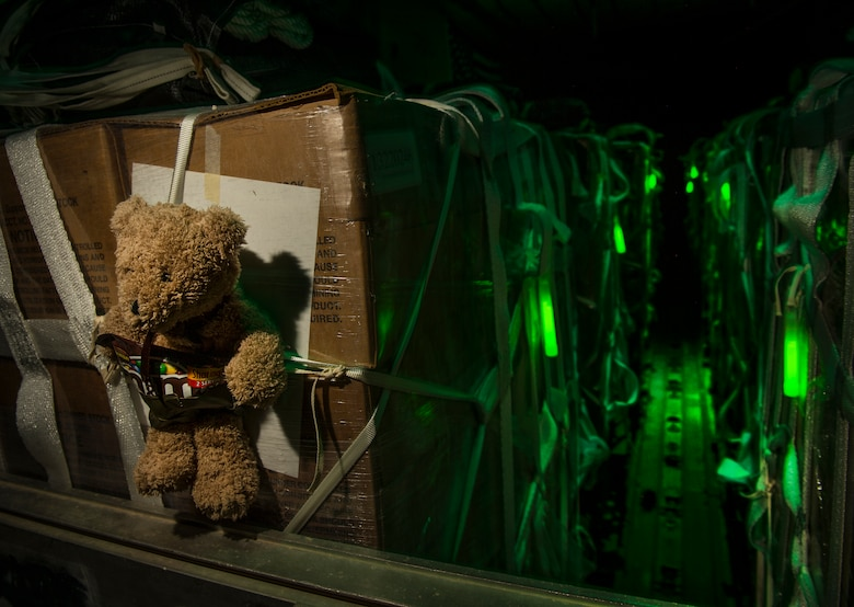 A teddy bear is tied to some humanitarian aid aboard a C-130 Hercules prior to take-off during an airdrop Aug. 14, 2014, over Iraq. The humanitarian aid includes bottled water and food which was delivered to displaced citizens in the vicinity of Sinjar, Iraq. The teddy bear was donated by an American child to pass along gratitude to children trapped in the Iraq conflict. The C-130 is assigned to the 746th Expeditionary Airlift Squadron. (U.S. Air Force photo/Staff Sgt. Vernon Young Jr.)