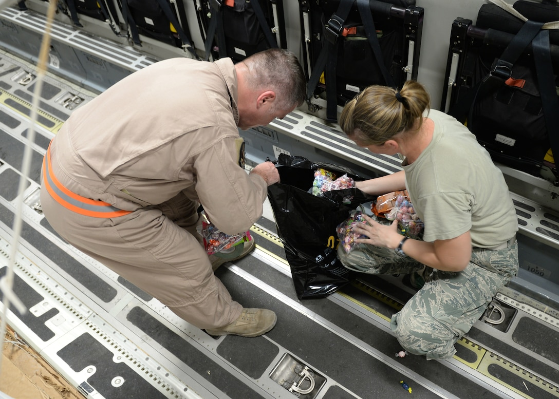 Master Sgts. Stephen Brown (left) and Emily Edmunds, 816th Expeditionary Airlift Squadron loadmasters, sort candy to attach to container delivery system bundles filled with fresh drinking water on a C-17 Globemaster III in preparation for a humanitarian airdrop  Aug. 30, 2014, over the area if Amirli, Iraq. The candy was collected by the squadron to supplement United States government humanitarian aid. (U.S. Air Force photo/Staff Sgt. Shawn Nickel)