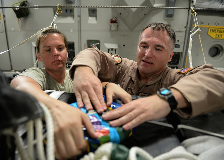 Master Sgts. Stephen Brown (right) and Emily Edmunds attach candy to container delivery system bundles filled with fresh drinking water on a C-17 Globemaster III in preparation for a humanitarian airdrop Aug. 30, 2014, over the area if Amirli, Iraq. The candy was collected by the squadron to supplement United States government humanitarian aid. Brown and Edmunds are 816th Expeditionary Airlift Squadron loadmasters. (U.S. Air Force photo/Staff Sgt. Shawn Nickel)
