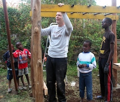 Brian Poole, a supervisory engineer in the U.S. Army Corps of Engineers Sacramento District engineering division, constructs new playground equipment alongside children from the Samaritan Village orphanage near Arusha, Tanzania. Poole was part of a volunteer team from Yuba City, California, that visited Tanzania on a mission trip in August 2014.