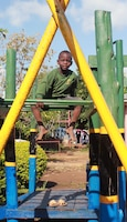 A young resident of Samaritan Village orphanage near Arusha, Tanzania, poses atop new playground equipment constructed in August 2014 by a volunteer team from Yuba City, California.