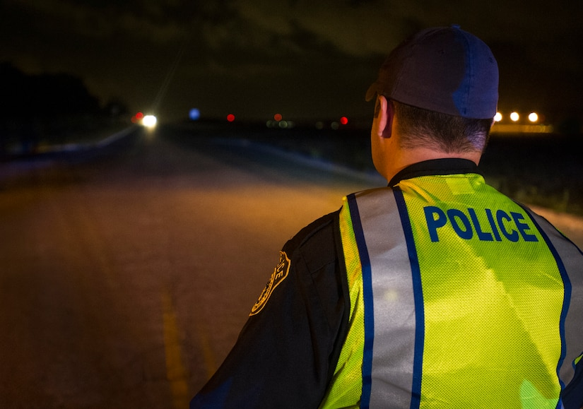 Andrew A. Drew 628th Security Forces Squadron patrolman waits as a car pulls up to a DUI checkpoint, Aug. 29, 2014, in North Charleston. The joint checkpoint allowed for officers from different agencies to gain a better understanding of how each department works. Holding DUI checkpoints help deter drivers from drinking and driving. (U.S. Air Force photo/Staff Sgt. William O'Brien)