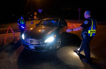 Robert Clark, 628th Security Forces Squadron patrolman, stops a car as it pulls up to a DUI checkpoint, Aug. 29, 2014, in North Charleston. The checkpoint was held as a joint effort between 628th Security Forces Squadron patrolmen and local sheriffs and police officers.  (U.S. Air Force photo/Staff Sgt. William O'Brien)