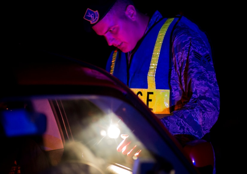 Senior Airman Michael Compson, 628th Security Forces Squadron patrolman, checks a driver's license during a DUI checkpoint, August 29, 2014, in North Charleston. The checkpoint was held as a joint effort between 628th SFS patrolmen and local sheriffs and police officers. (U.S. Air Force photo/Staff Sgt. William O'Brien)
