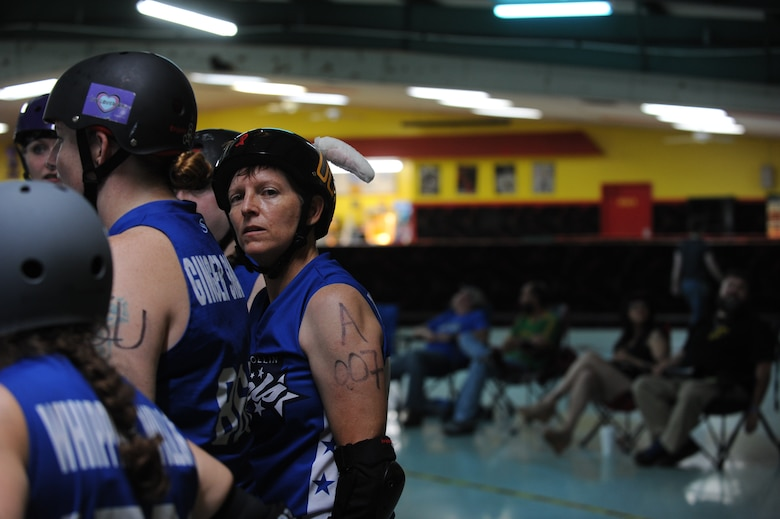 Lt. Col. Melanie Friedman, Curtis E. Lemay Center for Doctrine Development and Education deputy director of intelligence, enters a post-bout huddle with her roller derby team, the Capitol City Rollin' Rebels, Aug. 9, 2014, in Montgomery, Ala. The Rebels won against the Mobile Derby Darlins' 190-75. (U.S. Air Force photo by Staff Sgt. Natasha Stannard)