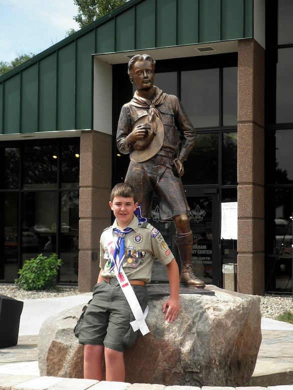 OMAHA, Nebraska – Dillon M. Duermyer, Eagle Scout, 14, poses for a photo next to a Dr. R. Tait McKenzie statue outside of the Mid-America Council Scout Headquarters June 11, 2010. The McKenzie statue is a visual representation of an ideal Boy Scout. The uncovered head represents reverence and obedience; the ax on which the hand rests is a symbol of George Washington's truthfulness. (Courtesy photo)