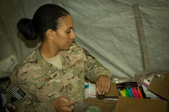 U.S. Air Force Master Sgt. Erin Lasker, 438th Air Expeditionary Advisory Group, helps sort and pack supplies for donation to family members of Afghan Air Force officers killed in a terrorist bombing July 2, 2014. A volunteer organization, Operation Outreach-Afghanistan, collected donations and presented them to the families of the fallen Afghan Airmen. (U.S. Air Force photo/Master Sgt. Eric B. Johnson)