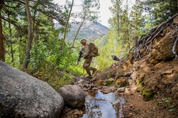 U.S. Marine Lance Cpl. Jona Moore tactically makes his way through the mountainous terrain with his squad during Mountain Exercise 2014 aboard Marine Corps Mountain Warfare Training Center in Bridgeport, Calif., Aug. 29, 2014. Moore is a team leader with 3rd Platoon, Lima Company, 3rd Battalion, 1st Marine Regiment. Marines with 3rd Battalion, 1st Marine Regiment will become the 15th Marine Expeditionary Unit's ground combat element in October. Mountain Exercise 2014 develops critical skills the battalion will need during deployment. (U.S. Marine Corps photo by Sgt. Emmanuel Ramos/Released)