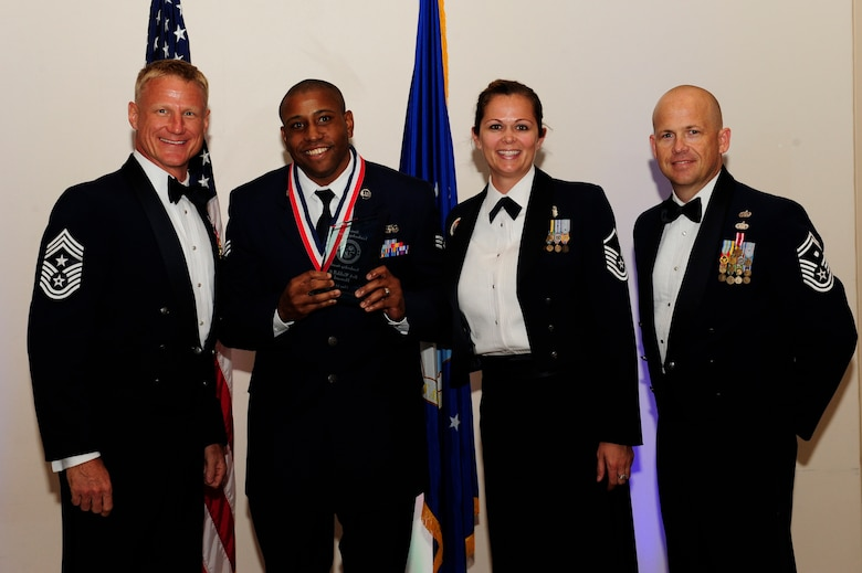 Senior Airman Waddell Howard, 460th Civil Engineer Squadron command program NCO in charge, second from left, receives the Leadership Award during the Buckley Airman Leadership School Class 14-F graduation Aug. 28, 2014, at the Leadership Development Center on Buckley Air Force Base, Colo. This award is presented to the ALS graduate who displays the best overall characteristics of an effective leader. (U.S. Air Force photo by Airman 1st Class Samantha Saulsbury/Released)
