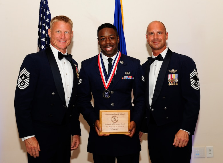 Senior Airman Wendell Hudnall, 460th Space Communications Squadron defense red switch network technician, center, receives the Academic Achievement Award during the Buckley Airman Leadership School Class 14-F graduation Aug. 28, 2014, at the Leadership Development Center on Buckley Air Force Base, Colo. The award is presented to the student with the highest overall average on all academic evaluations during ALS. (U.S. Air Force photo by Airman 1st Class Samantha Saulsbury/Released)