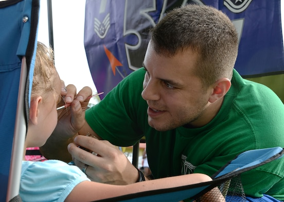 Staff Sgt. Robert Terwilliger, 36th Communications Squadron, paints a child's face during the 2014 Labor Day Bash Sept. 1, 2014, on Andersen Air Force Base, Guam. The annual event featured several attractions such as carabao rides, raffle drawings and a pie-eating contest. (U.S. Air Force photo by Senior Airman Katrina M. Brisbin/Released)