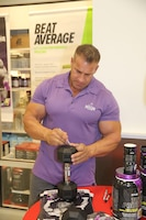 Jay Cutler, professional bodybuilder, autographs a fan's dumbbell at a promotional appearance at the GNC in the Main Exchange, Aug. 28, 2014.