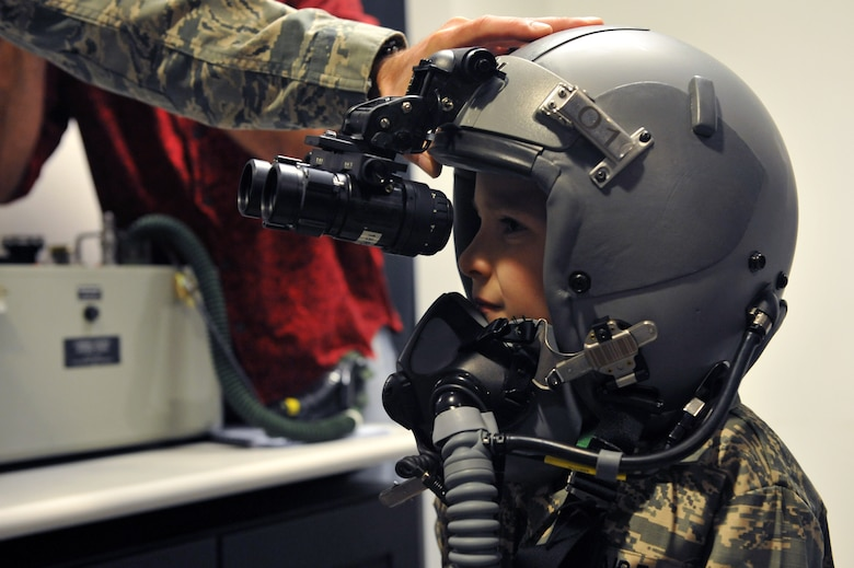 Keegan Stipe, left, a 7-year-old boy who is overcoming transverse myelitis, a spinal condition that limits his ability to walk, tries on pilot gear during his Airman for a Day base tour Aug. 26, 2014, on Buckley Air Force Base, Colo. Keegan has always been fascinated with fast planes, loud guns and the military lifestyle, so the 460th Space Wing gave him and his parents the opportunity to visit the base. On his tour, he visited the 140th Wing, Air National Guard and various 460th SFS sections. (U.S. Air Force photo by Airman Emily E. Amyotte/Released)