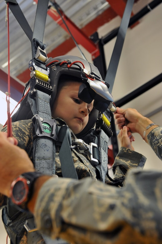 Keegan Stipe, left, a 7-year-old boy who is overcoming transverse myelitis, a spinal condition that limits his ability to walk, simulates landing a parachute during his Airman for a Day base tour Aug. 26, 2014, on Buckley Air Force Base, Colo. Keegan has always been fascinated with fast planes, loud guns and the military lifestyle, so the 460th Space Wing gave him and his parents the opportunity to visit the base. On his tour, he visited the 140th Wing, Air National Guard and various 460th SFS sections. (U.S. Air Force photo by Airman Emily E. Amyotte/Released)