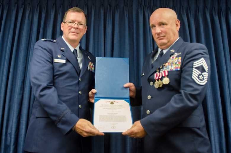 Chief Master Sgt. Daniel Fuller (right), the outgoing superintendent of the Kentucky Air National Guard's 123rd Operations Group, is awarded the Meritorious Service Medal by Col. Robert Hamm, commander of the Operations Group, during Fuller's retirement ceremony at the Kentucky Air National Guard Base in Louisville, Ky., June 8, 2014.  Fuller retired after 36 years of service. (U.S. Air National Guard photo by Senior Airman Joshua Horton)