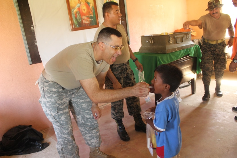 U.S. Army Capt. Manuel Bucardo coaxes a Honduran child to take de-wormer medication during a medical readiness training exercise Aug. 25-28 in the remote village of Rio Platano, Department of Gracias a Dios, Honduras.  MEDEL partnered with the Honduran Ministry of Health and the Honduran military to provide classes for the patients to teach them about hygiene, nutrition, and preventative dental practices.  They also provide wellness checkups, medication, dental care, and perform minor medical procedures as required.  (Photo by U.S. Army Spec. Anthony Gonzales)