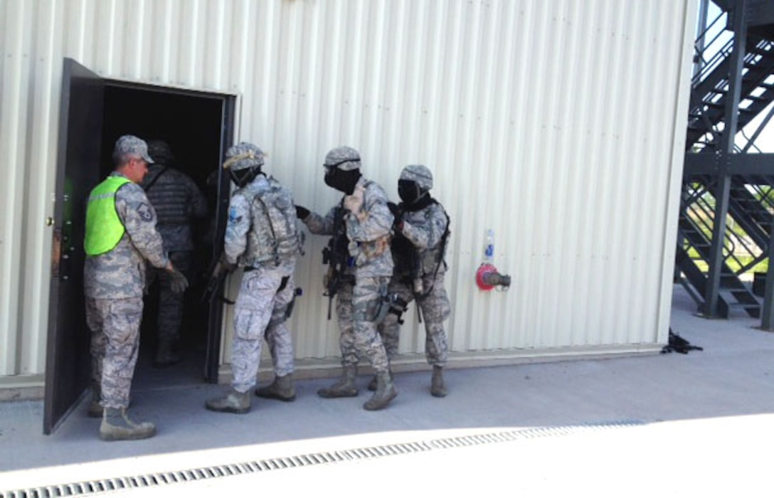 Members of the 914th Security Forces Squadron demonstrate breaching procedures at Niagara Falls Air Reserve Station on June 9, 2014. Personnel were participating in an active shooter exercise here. (U.S. Air Force photo by 1st Lt. Brian Rhoney)