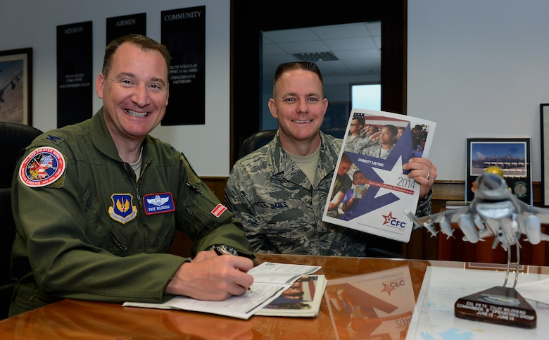 U.S. Air Force Col. Pete M. Bilodeau, 52nd Fighter Wing commander, left, and U.S. Air Force Chief Master Sgt. Brian J. Gates, 52nd FW command chief, make donations through the Combined Federal Campaign-Overseas at Spangdahlem Air Base, Germany, Sep. 3, 2014.  The CFC-O is a charity fundraiser that allows people to donate money to more than 2,500 organizations to help those in need. (U.S. Air Force photo by Airman 1st Class Luke J. Kitterman/Released)
