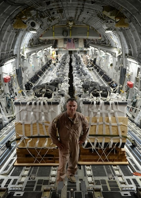 Air Force Master Sgt. Stephen Brown poses in front of 40 container delivery system bundles filled with fresh drinking water on a C-17 Globemaster III in preparation for a humanitarian airdrop over the area of Amirli, Iraq, Aug. 30, 2014. Brown taped candy to most of the bundles in hopes of bringing cheer to displaced Iraqi children. U.S. Air Force photo by Staff Sgt. Shawn Nickel