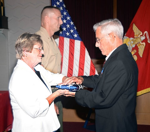 Both with Marine Corps Systems Command, Shirley Lemon presents Fred Day with a national ensign during his retirement ceremony Aug. 28 at the Chapel of the Good Shepherd, here. Day retired after nearly 40 years of military and civil service.