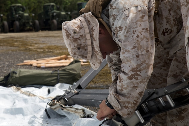 A Marine works to set up a tent Sept. 1 on Tinian during preparation for Exercise Valiant Shield 2014. The squadron's mission during the exercise is to prepare an airstrip and provide support for all participating units. Valiant Shield is a biennial exercise which focuses on the integration of joint training among U.S. forces. The Marine is with Marine Wing Support Squadron 171, Marine Aircraft Group 12, 1st Marine Aircraft Wing, III Marine Expeditionary Force.