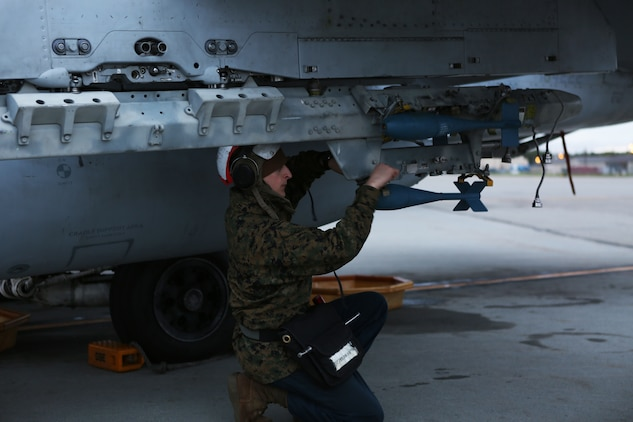 Lance Cpl. Matt Sisk, an ordnance technician with Marine Fighter Attack Squadron 122, adjusts the bracket on a BRU-41 multiple ejector rack while loading a MK-76 practice bomb onto an F/A-18C Hornet, Sept. 3, 2014, aboard Eielson Air Force Base, Alaska. The Hornet was loaded with ordnance for a bombing mission as part of the squadron's unit level training, named Distant Frontier.