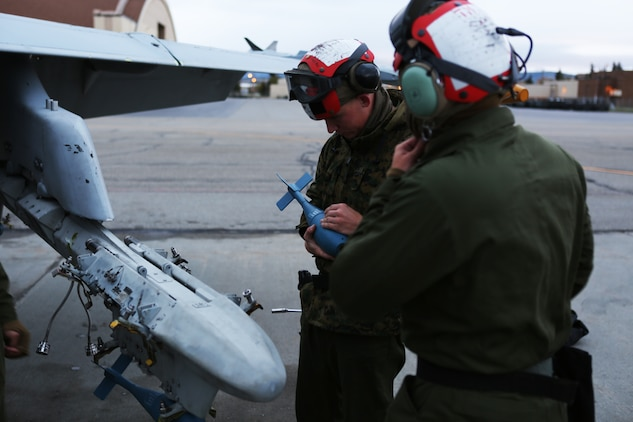 Lance Cpl. Corey Lords, an ordnance technician with Marine Fighter Attack Squadron 122, adjusts a lug on a MK-76 practice bomb to ensure it properly attaches to a BRU-41 multiple ejector rack attached to an F/A-18C Hornet, Sept. 3, 2014, aboard Eielson Air Force Base, Alaska. The Hornet was loaded with ordnance for a bombing mission as part of the squadron's unit level training, named Distant Frontier.