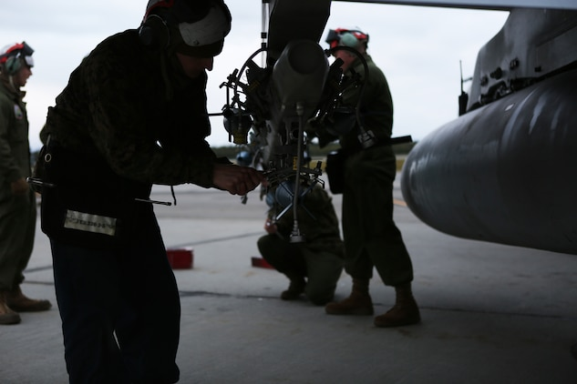 An ordnance technician with Marine Fighter Attack Squadron 122 adjusts the bracket on a BRU-41 multiple ejector rack while loading a MK-76 practice bomb onto an F/A-18C Hornet, Sept. 3, 2014, aboard Eielson Air Force Base, Alaska. The ordnance Marines loaded more than 20 MK-76 practice bombs onto four F/A-18C Hornets for a bombing mission as part of the squadron's unit level training, named Distant Frontier.