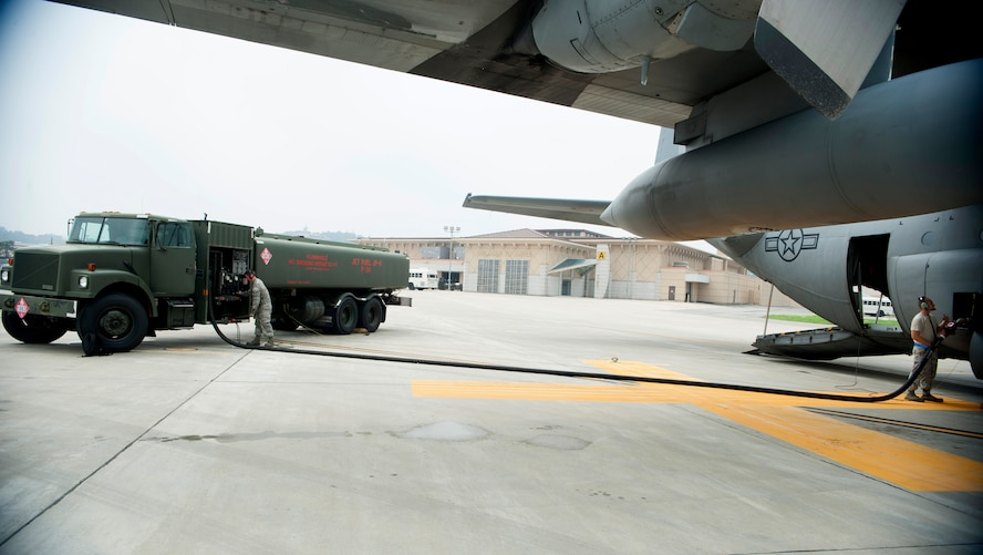 Airman 1st Class Jamie Groseclose, 51st Logistics Readiness Squadron fuels operator (left), fuels a C-130 Hercules while a C-130 crew chief monitors the fuel flow at Osan Air Base, Republic of Korea, Aug. 5, 2014. The fuels flight issues fuel to fighter jets within the 25th and 36th Fighter Squadrons as well as cargo and passenger transportation aircraft that fly in and out of the base. (U.S. Air Force photo by Senior Airman Matthew Lancaster/Released)
