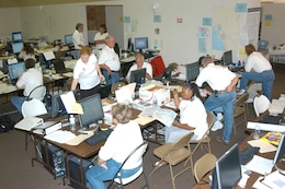 "Workers staff an Army Corps of Engineers Emergency Response & Recovery Office (ERRO) following the 2004 hurricanes in Florida.  The purpose of the recovery field office is the management and execution of FEMA recovery missions assigned to the Corps.  In 2004, those missions included temporary roofing (a/k/a the ""Blue Roof"" Program), temporary housing, power, ice, and water."