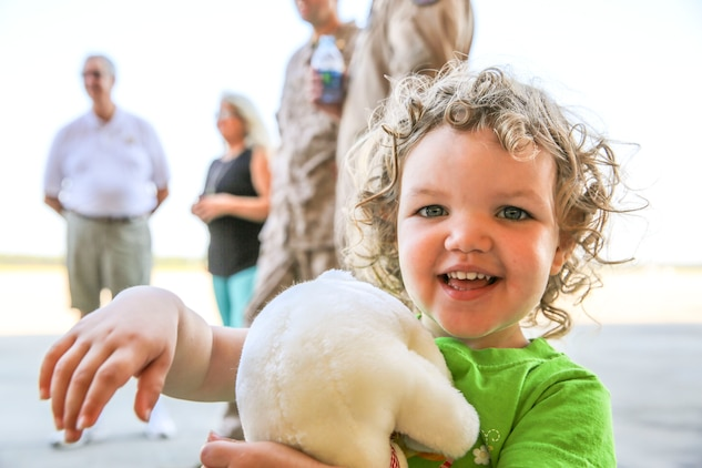 Aria Condi hugs her new stuffed polar bear from the USO as her father, Capt. Jason Condi, a pilot with Marine All-Weather Fighter Attack Squadron 533, prepares to deploy, Sept. 2. The deployment will help maintain relations with allied countries in the region.