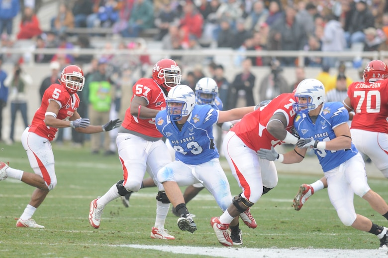 Air Force Falcons defensive lineman Ben Garland, left in blue uniform, and defensive end Myles Morales slip past members of the University of Houston Cougars during the Armed Forces Bowl Dec. 31, 2009, in Fort Worth, Texas. The Air Force Academy won the game 47-20. (U.S. Air Force photo/Bill Evans)
