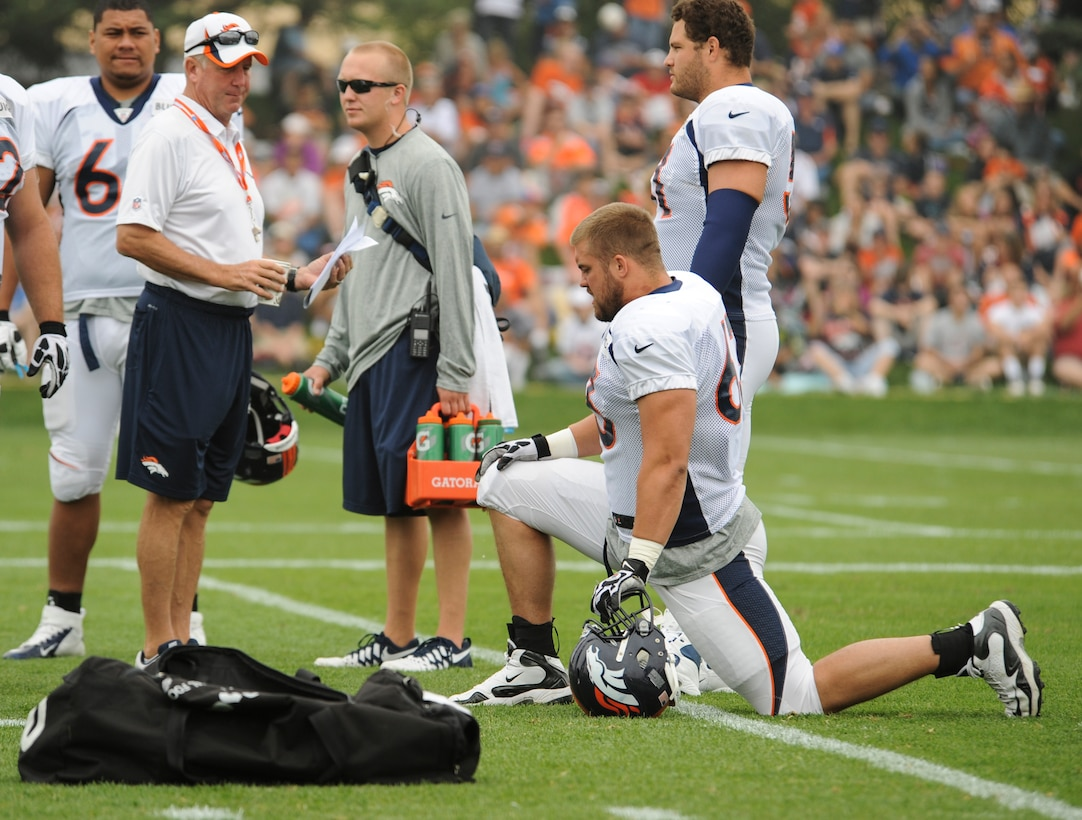 Ben Garland, Denver Broncos offensive guard, kneeling, listens to head coach John Fox before a Broncos training camp practice July 29, 2013, at the Broncos training facility in Englewood, Colo. Garland spent the 2012 season on the Broncos practice squad and transitioned from defensive tackle to offensive guard before the Broncos 2013 mini-camp. Garland is also a public affairs officer with the 140th Wing, Colorado Air National Guard, and served his annual commitment during the early part of 2013. (U.S. Air Force photo/Staff Sgt. Christopher Gross)