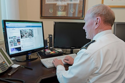 Army Gen. Martin E. Dempsey, chairman of the Joint Chiefs of Staff, communicates with service members as he hosts a Facebook town hall meeting from his office at the Pentagon, Sept. 4, 2014.