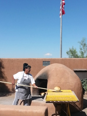 "COCHITI LAKE, N.M., -- Cochiti Tribal member Marian Valdo takes baked bread out of the the ""Kuush-Ku,"" – the bread oven – located in the Visitor Center courtyard, Aug. 9, 2014. This was the first time the ""Kuush-Ku"" was used for its intended purpose."