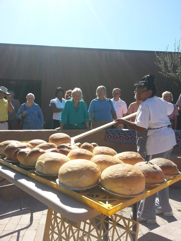 "COCHITI LAKE, N.M., -- Attendees at the  Aug. 9, event watch as Marian Valdo brings bread out of the ""Kuush-Ku"" or bread oven, located in the Visitor Center Courtyard.  This was the first time the oven was used to bake bread."