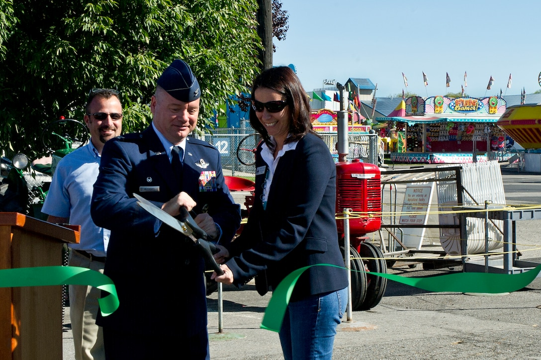 Col. Brian McDaniel, the 92nd Air Refueling Wing commander, joins Shelly O'Quinn, Spokane County Commissioner for District 2, in a ribbon cutting ceremony to commemorate the opening of the Spokane Interstate Fair in Spokane, Washington, Sept. 5, 2014. Spokane County's Interstate Fair is a 10-day event beginning the Friday after Labor Day each year. The Fair is held at the Spokane County Fair and Expo Center on the corner of Broadway and Havana, its location since 1952. (U.S. Air Force photo by Staff Sgt. Alexandre Montes/Released)