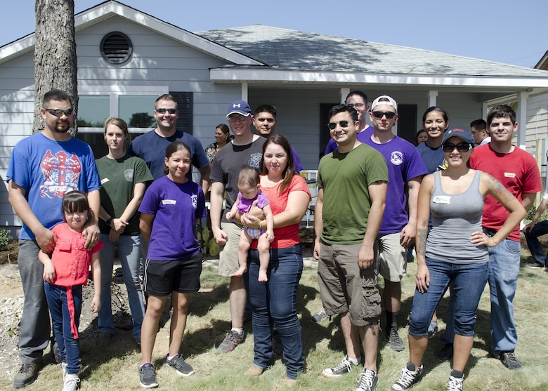 The Gonzalez family, recipients of a new home from Habitat for Humanity, stand with Air Force volunteers who helped make their home a reality in San Antonio, Texas, Aug. 22.
