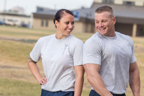 (Left) Staff Sgt. Tanisha Chaney, a 37th Training Support Squadron combat weapons instructor, and her husband, Tech Sgt. Eric Chaney, 37th TRSS NCO in charge of combat operations flight, smile at each other after a workout outside the Warhawk Fitness Center, Joint Base San Antonio-Lackland. (U.S. Air Force Photo by Joshua Rodriguez/Released)