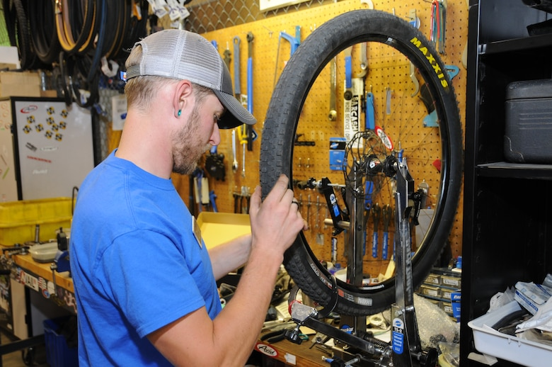 Seth Michael, a 10th Force Support Squadron Outdoor Rec Center employee, trues a mountain bike tire at the center here. The center is gearing-up to provide a variety of winter services for Academy Airmen and their families. (U.S. Air Force photo)