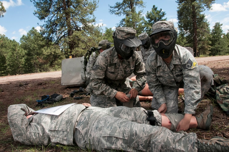 Tech. Sgt. Christine Yebra and Staff Sgt. Cory Zehner put their self-aid and buddy care skills to the test while keeping an eye out for enemy gun fire during the care-under-fire exercise. More than 70 Airmen from the 162nd Wing ventured up to the cool pines of Bellemont, Ariz. during a training exercise Aug. 11-15 at Camp Navajo Collective Training Center. (U.S. Air National Guard photo by 2nd Lt. Lacey Roberts)