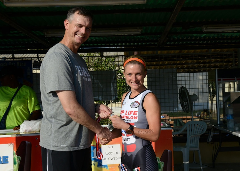 Tech. Sgt. Jessica Pigott, 717th Air Base Squadron logistics contract manager, receives a medal for being the first place female competitor during a sprint triathlon, Aug. 9, 2014, Incirlik Air Base Turkey. Pigott received U.S. Air Forces in Europe and Air Forces Africa,  female athlete of the year for 2014. (U.S. Air Force photo by Staff Sgt. Veronica Pierce/Released)